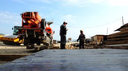 állványzat : workers at the construction site stand at the truck crane in discussing work plans Stock mozgókép