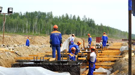 marco internacional : a group of working people and builders perform installation work on the foundations of the building