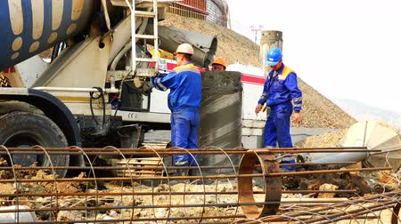 kırsal : Workers at the construction site receive concrete from a concrete mixer and poured into a casing into a casing