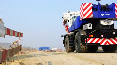 talaj : movement of a self-propelled crane on wheels along a protective fence along a dirt road Stock mozgókép