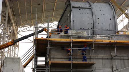 enriching : workers mount a grinding mill for ores of ferrous and non-ferrous metals at a concentrating mill Stock Footage