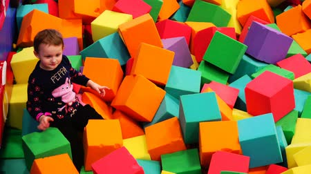 яма : The boy makes faces lying in the bath of foam soft cubes