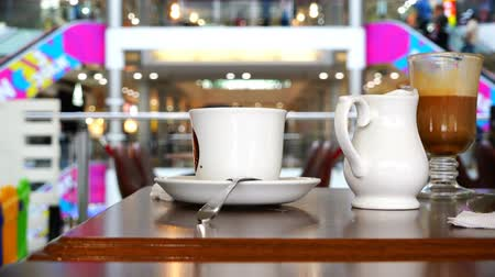 cümbüş : hand raises a cup of coffee from a saucer at a table in a cafe