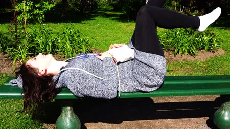 só as mulheres jovens : young girl dances to music lying on bench in park Vídeos