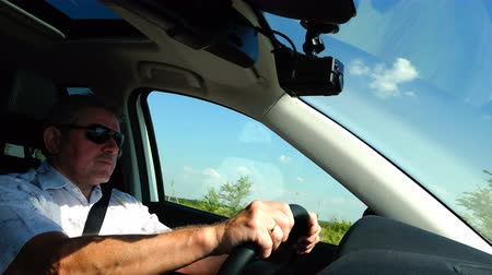 limuzína : a man in a white shirt and sunglasses is driving a car Dostupné videozáznamy