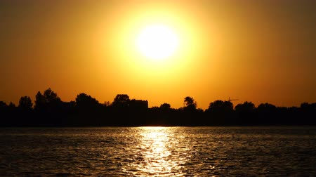 quiet evening : bright yellow sun over the river Stock Footage