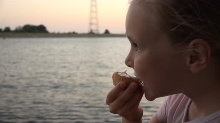 small vessels : a girl on a boat eating an ice cream and looking out into the distance