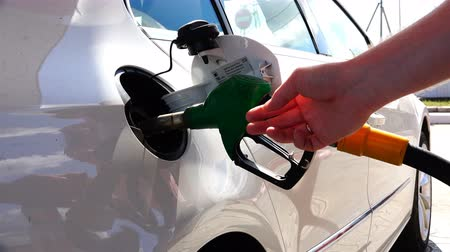 galão : The car owner removes the fuel gun from the tank after refueling the car