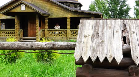 bell tower : An elderly grandmother sits on the veranda of a wooden church Stock Footage