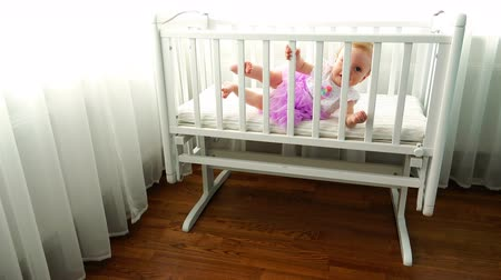 szopka : a child leans on the side of a white childs cot in the bedroom.