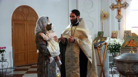 baptism : the priest in the church tells the canons of the mother with the child in his arms