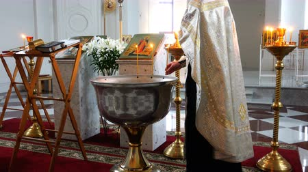 посвящение : the priest lights the burning candle with water in the font for the ritual of baptism.