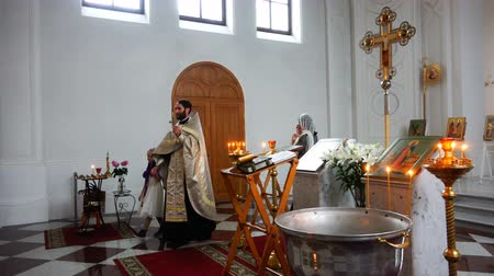 christening : ritual of baptism in the Orthodox Church with a cross in hands