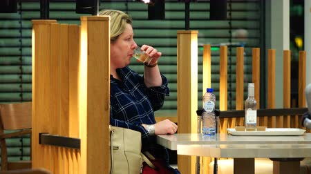 franczyza : Netherlands, November 21, 2017, Amsterdam Airport Schiphol, a single woman drinks white wine from a plastic glass at a table in a cafe Wideo