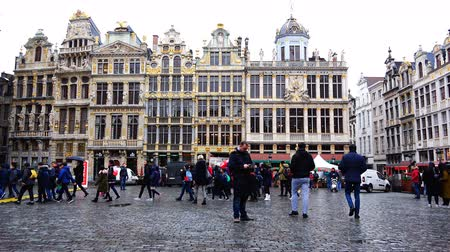 pozlacený : Belgium, November 24, 2017, Brussels Grand Place Square A building with golden ornaments, past which schoolchildren