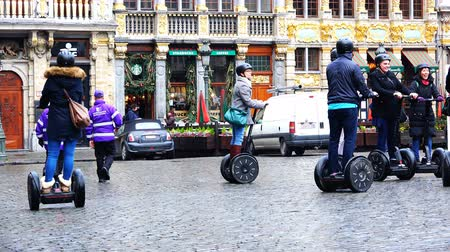 self balancing : Belgium, November 24, 2017, Brussels Grand Place Plaza, a company of people in spring clothes ride on gyro pacemakers on paving stones