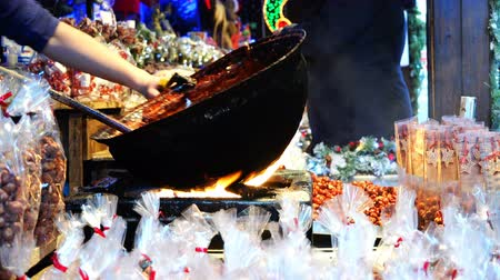 lezzet : A cook cooks in the street cooking on a fire in a large black bowl. Stok Video