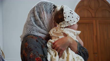 christening : mother and child with headscarves on the ministry in the church. Stock Footage
