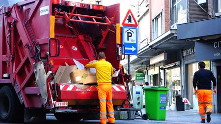 kolektor : Belgium, 22 November 2017, Leuven, garbage truck presses empty cardboard boxes that are folded into the body of the cleaning company employees