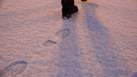 otisk : girl walking through the snow in winter boots, leaving behind traces.
