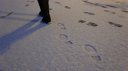 voetstappen : a woman in boots steps on top of the snow leaving footprints in the snow. Stockvideo