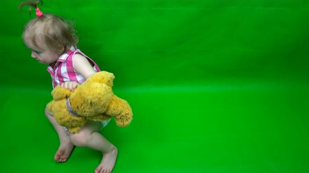 hromakey : the child is kissing a teddy bear on a green background. Chromakey.