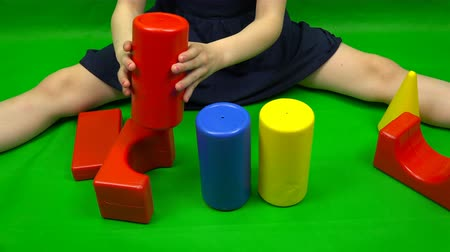 hromakey : the child builds a tower of cubes of blue, yellow and red.