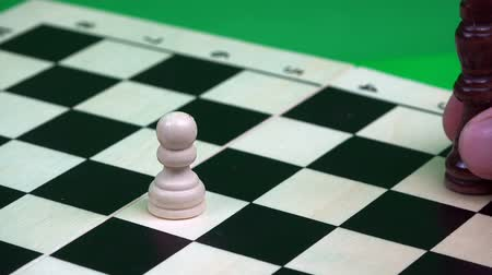 peão : a white pawn is cut by a black king on a chessboard.