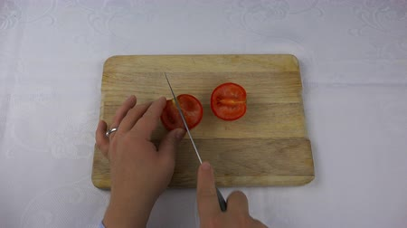 ingrediente : a sharp knife cuts a red tomato into four pieces.