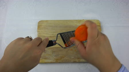 aprított : the cook is rubbing carrots on a small grater.