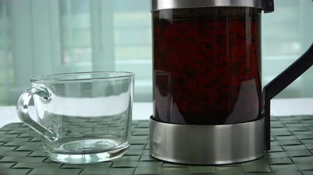csöpögő : a glass teapot with strong brewed tea stands next to the cup.