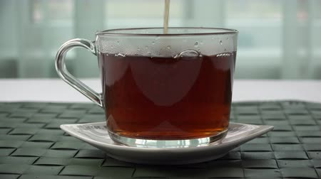 tea bag : a stream of tea is poured into a glass cup.