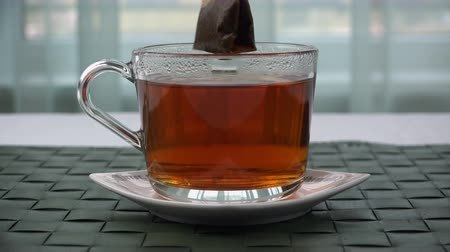 fincan tabağı : a tea bag is taken from a cup of tea. Stok Video
