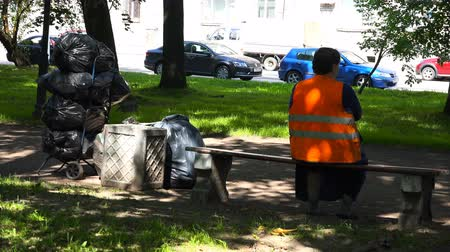 újrahasznosított : a woman in a special form is resting on a bench after cleaning the territory.