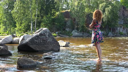plage : a girl stands barefoot on a stone in the water.