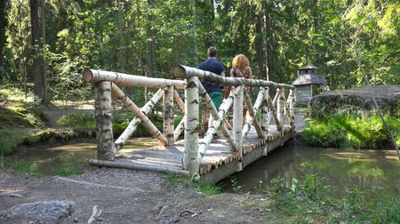wooden bridge : a young couple walking on a wooden bridge in the park.