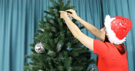 maiden : woman in red Christmas outfit decorates the Christmas tree Stock Footage
