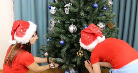 átölelő : boy with mom in christmas caps decorate new year tree