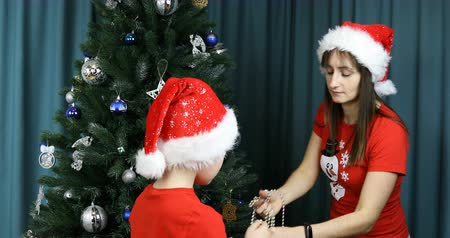 бежевый : Mother and son unwind holiday beads on the Christmas tree