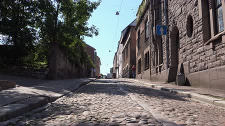 paving : man climbs up a cobblestone narrow street.