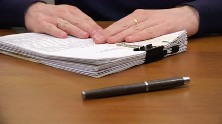 documentation : Hands move a stack of documents to the pen on the table.