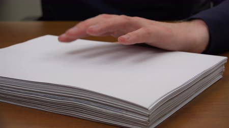 bürokrasi : Fingers of the left hand alternately tap on the stack of paper.