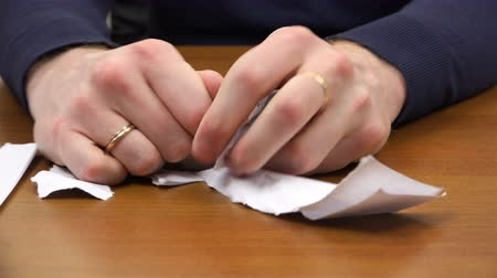 rejeitar : Fingers of hands tearing sheets of paper on the table.