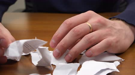 em branco : Hands go through ripped pieces of paper on the table. Vídeos