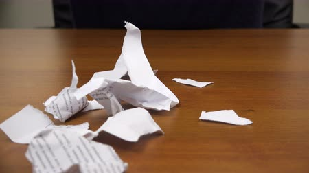 бумага : Torn pieces of paper fall on the table. Стоковые видеозаписи