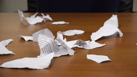 broszura : Torn pieces of a document fall on top with scraps on the table.