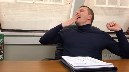 fárasztó : The office employee is yawning at the workplace and falls asleep on a stack of documents. Stock mozgókép