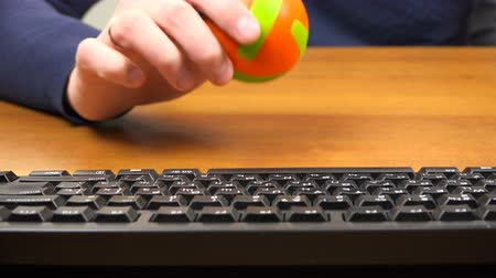basketball : A man plays with a small ball on the desktop.