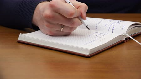 memo : A man writes a white pen. Stock Footage