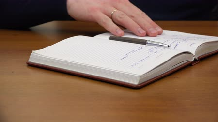 diary : Mens hand puts a pen on a notebook. Stock Footage